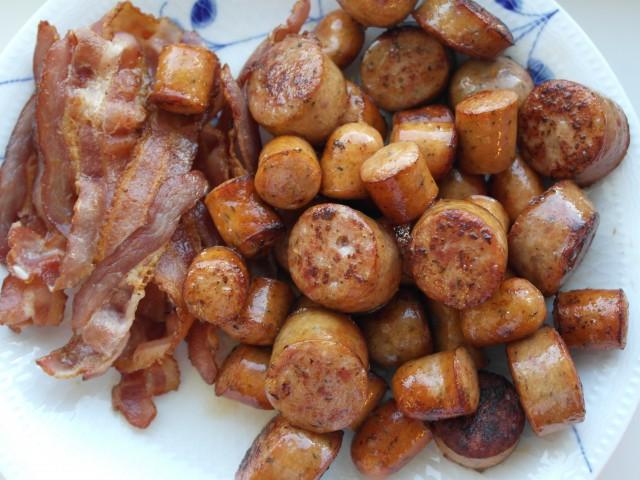 Bacon og pølser som er stegt på panden